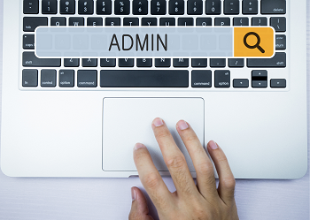 Admin hand on laptop keyboard